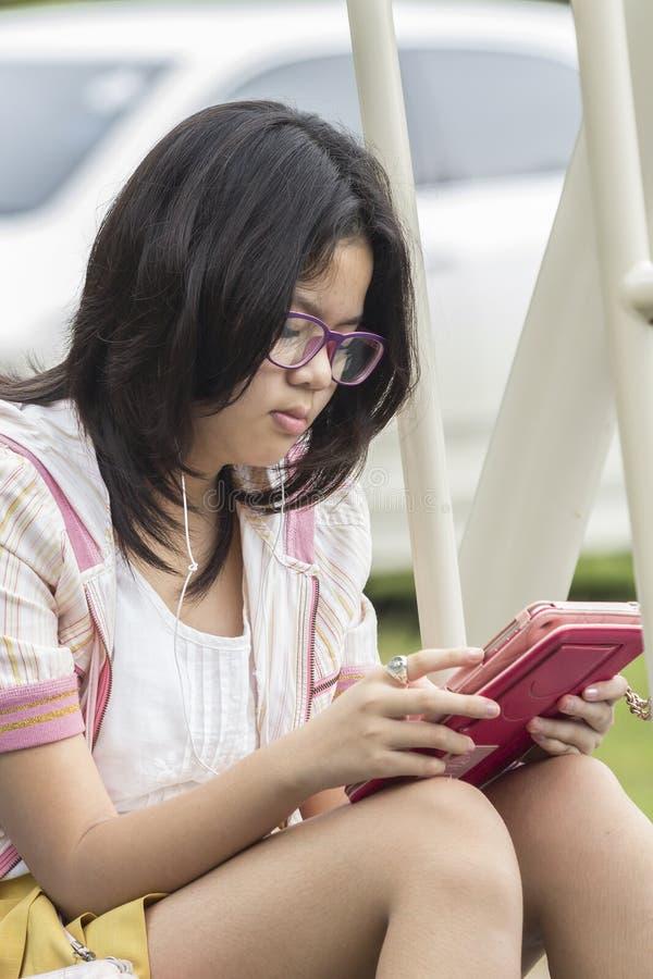 Thailändsk flicka som kopplar av med den digitala minnestavlan royaltyfria bilder