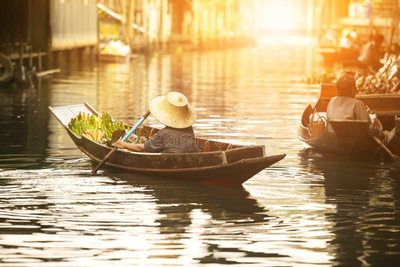 Thailändsk fruktsäljare som seglar träfartyget i Thailand tradition som svävar marknaden arkivbild