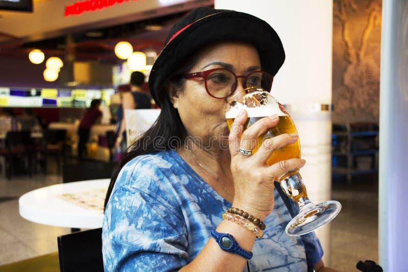 Thailändsk gammal kvinna som dricker tjeckisk stil för öl royaltyfria bilder