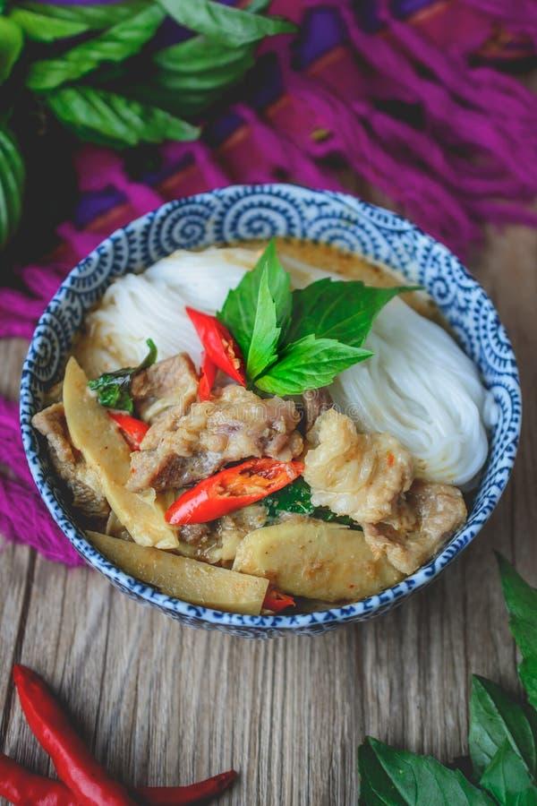 Thailändsk grön curry med griskött på thailändskt tyg och gamla träBackgr royaltyfri bild