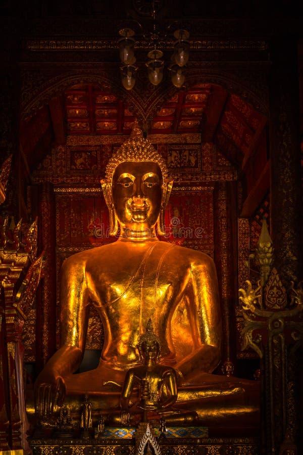 Thailändsk guld- buddha vertikal mörk guld- fredstillhet arkivfoto