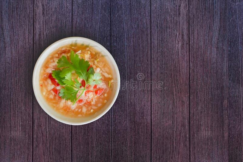 Thailändsk havs- doppa sås för bästa sikt i den vita bunken Gör från vitlök, den röda chili, fisksås, salta, socker, limefruktfru arkivfoton