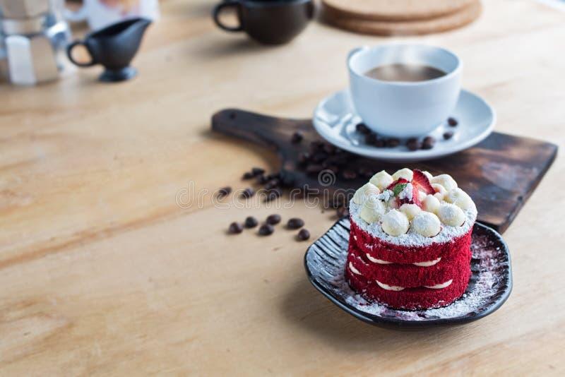Thailändsk kaka och kaffe Röd kaka för sammet Kakor dekorerade med den röda kakan på den trätabellen och blomman jordgubbemorgon  royaltyfria bilder