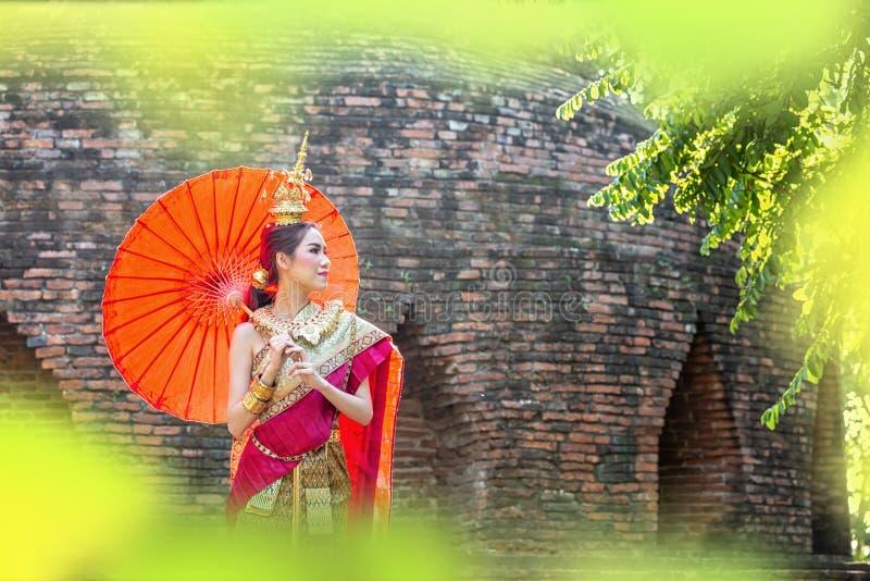 Thailändsk kvinna i traditionell dräkt med paraplyet av Thailand Kvinnlig traditionell dräkt med thai stiltempelbakgrund wat fotografering för bildbyråer