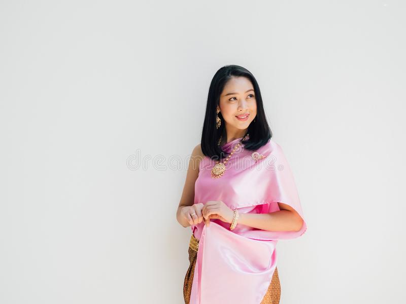 Thail?ndsk kvinna i thail?ndsk traditionell dr?kt p? gr? bakgrund arkivfoton