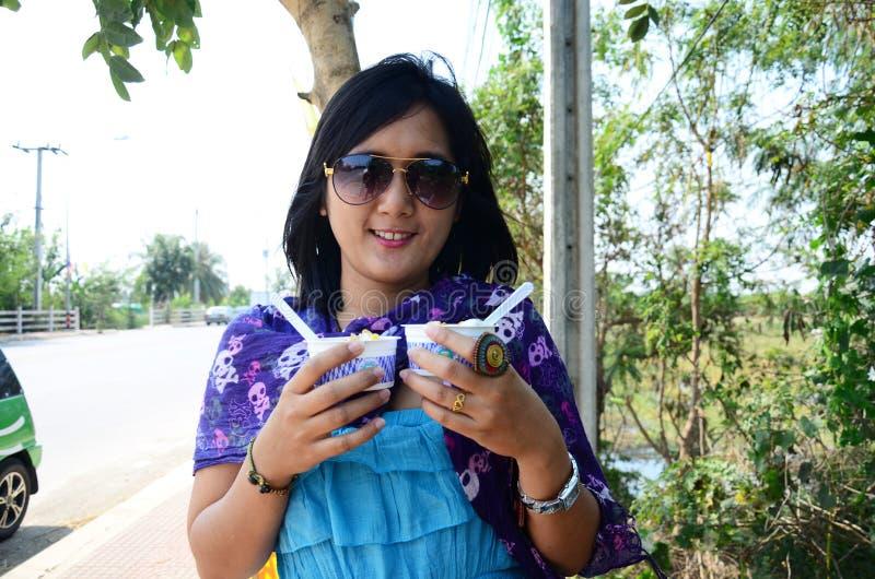 Thailändsk kvinna som äter glass arkivbilder