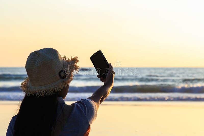 Thailändsk kvinna som använder smartphonen på stranden royaltyfria bilder