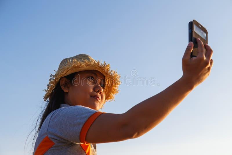 Thailändsk kvinna som använder smartphonen på stranden royaltyfri bild