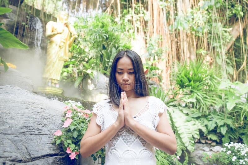 Thailändsk kvinna som ber i en buddistisk tempel royaltyfri fotografi