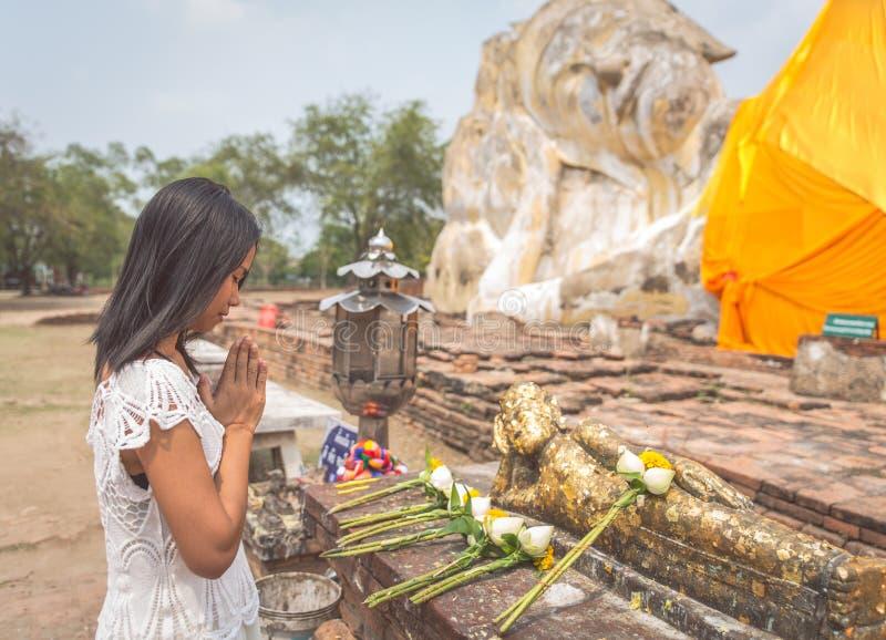 Thailändsk kvinna som framme ber i den Ayutthaya templet den stora buddhaen royaltyfri bild