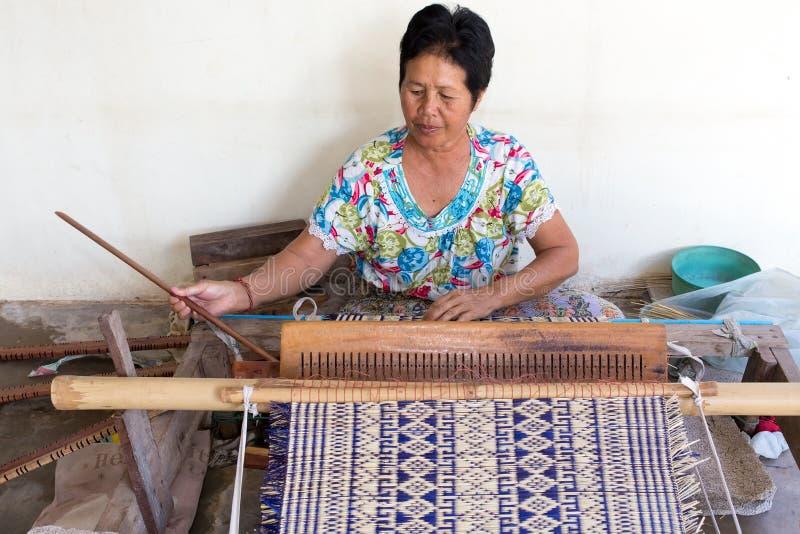 Thailändsk kvinna som väver mattt sugrör fotografering för bildbyråer