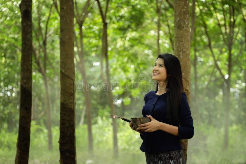 Thailändsk kvinna under gummiträden royaltyfria foton