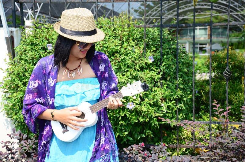 Thailändsk kvinnalekukulele eller liten akustisk gitarr royaltyfri fotografi
