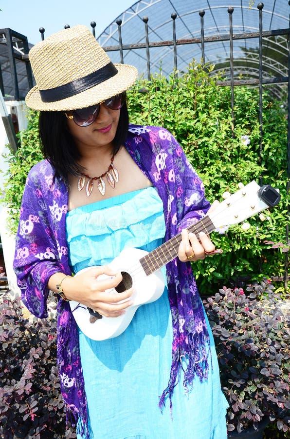 Thailändsk kvinnalekukulele eller liten akustisk gitarr royaltyfria foton