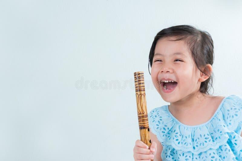 Thailändsk liten gullig flicka i den traditionella klänningen som spelar thailändsk bambu F arkivfoton