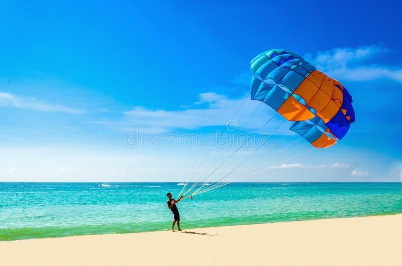 Thailändsk man som av tar parasail på stranden, Thailand royaltyfri foto