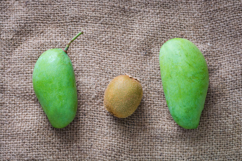 Thailändsk mango, tropisk frukt för kiwi på traditionellt tyg royaltyfria bilder