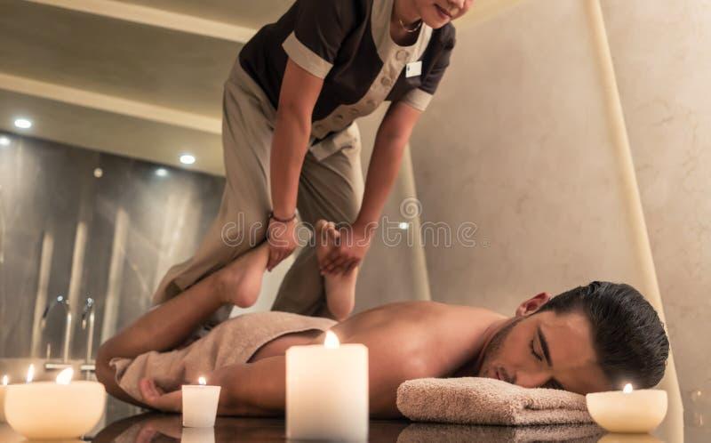 Thailändsk massagepraktiker som masserar mannen till och med sträckning av techn royaltyfri fotografi