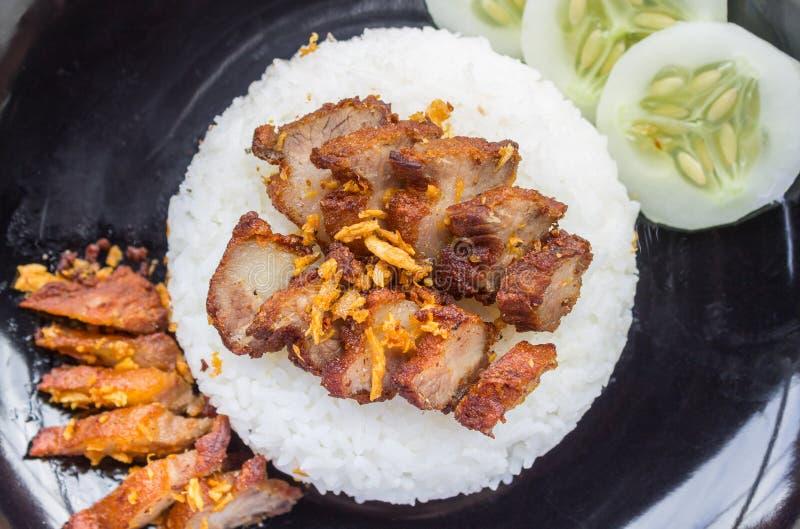 Thailändsk mat Fried Pork med vitlök och gurkan i svart maträttlägenhet royaltyfria bilder