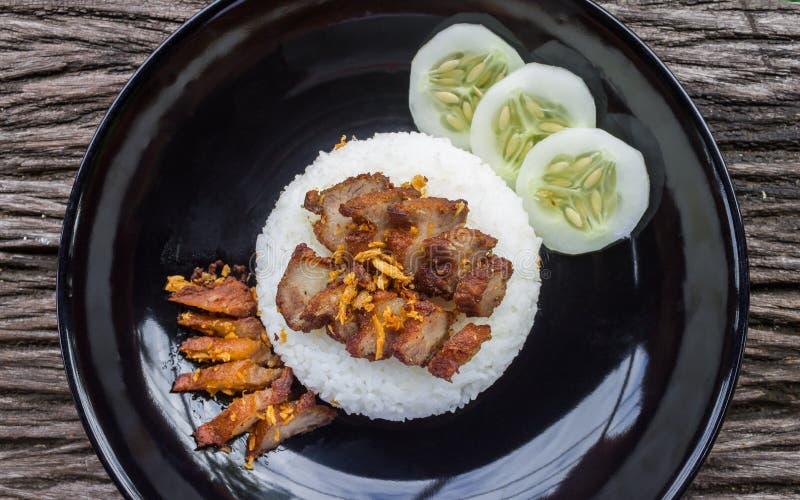 Thailändsk mat Fried Pork med vitlök och gurkan i svart maträttlägenhet royaltyfri foto