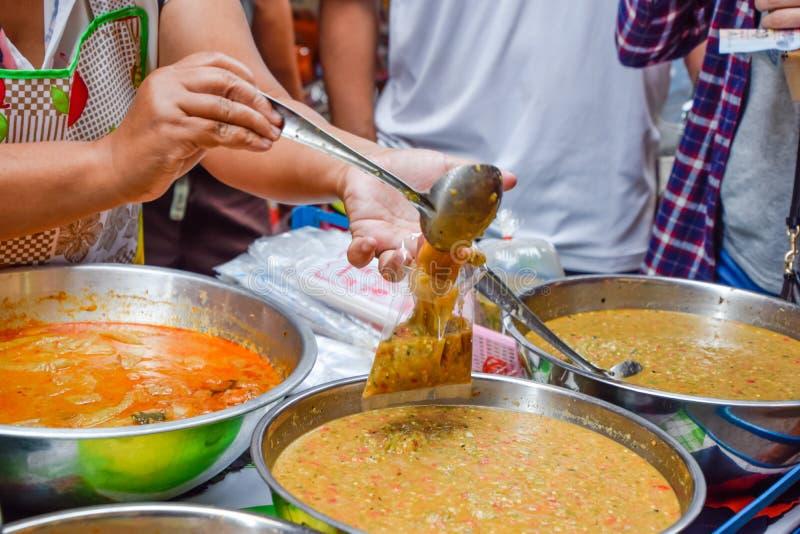 Thailändsk mat - gammal kvinna som säljer mat på marknaden fotografering för bildbyråer