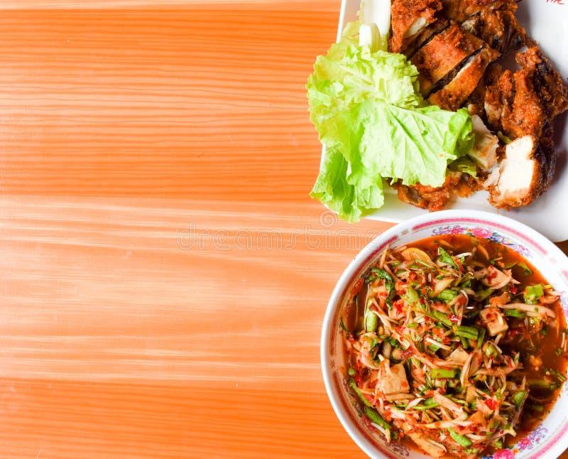 Thailändsk mat (KAIYANG-SOMTUM): Panaya kryddig sallad med den rimmade krabban och grillade fega och klibbiga ris royaltyfria bilder