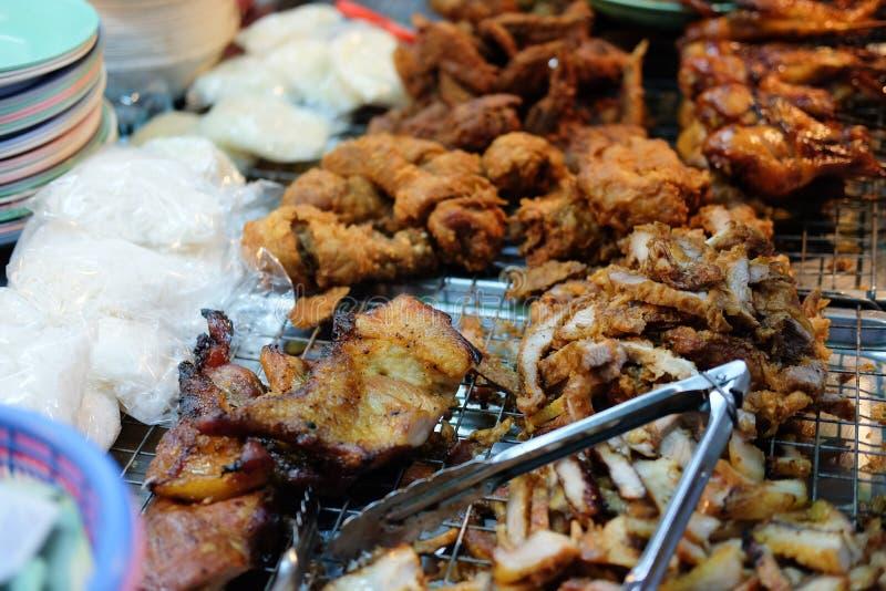 Thailändsk mat på marknadsför Grillat kryddigt griskött, stekt griskött fotografering för bildbyråer