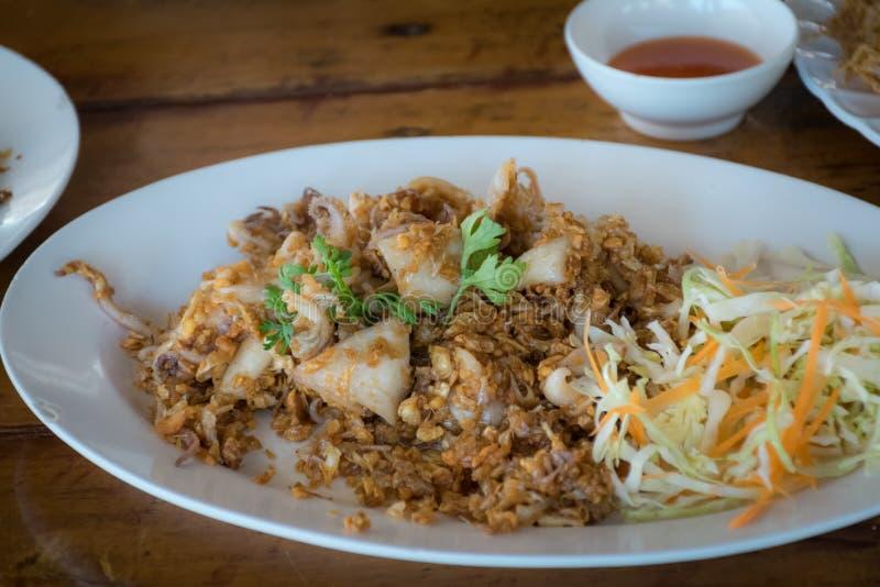 Thailändsk mat, tioarmad bläckfisk som stekas under omrörning med vitlök, och pepparkorn arkivbilder