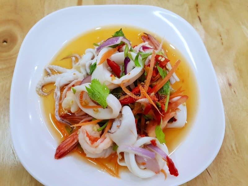 Thailändsk matstil, bästa sikt av kryddig thailändsk havs- sallad på den vita plattan på trätabellen arkivfoto