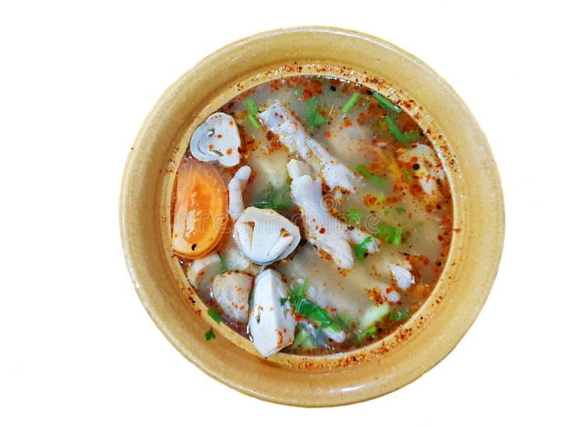 Thailändsk matstil, bästa sikt av kryddig soppa för feg fot med tomaten, champinjon, chili och koriander i den isolerade gula bun arkivbilder