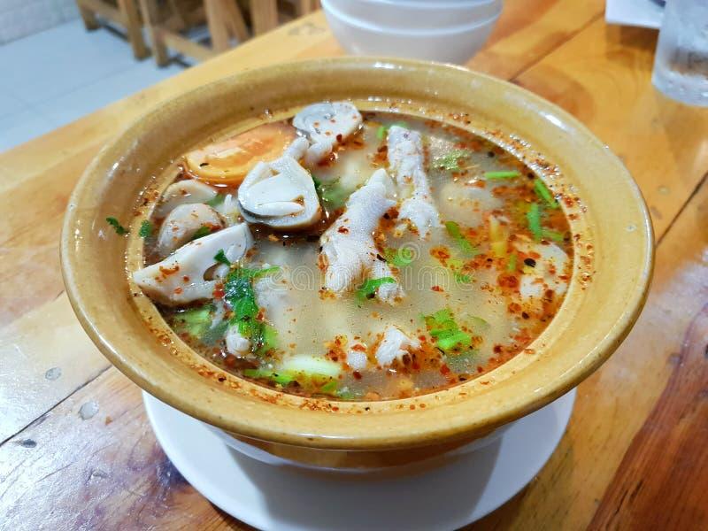 Thailändsk matstil, Closeup av kryddig soppa för feg fot med tomaten, champinjon, chili och koriander i gul bunke på trätabellen arkivbilder