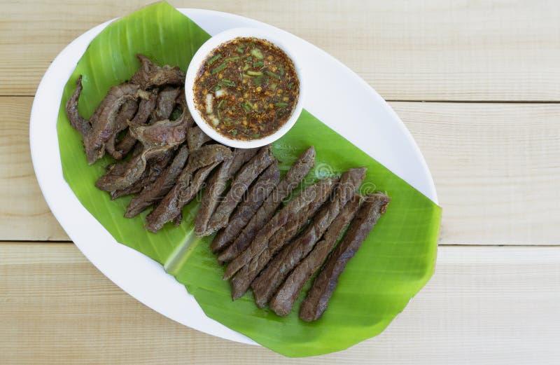 Thailändsk matstil för grillfest i en vit maträtt på trägolvtabellen, royaltyfria bilder