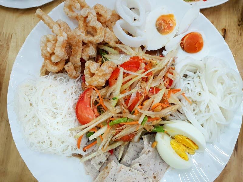 Thailändsk matstil, Papayasallad med tomaten, räka, chili, böna, rimmat ägg, knäcka för griskött och risvermiceller på den vita p royaltyfria foton