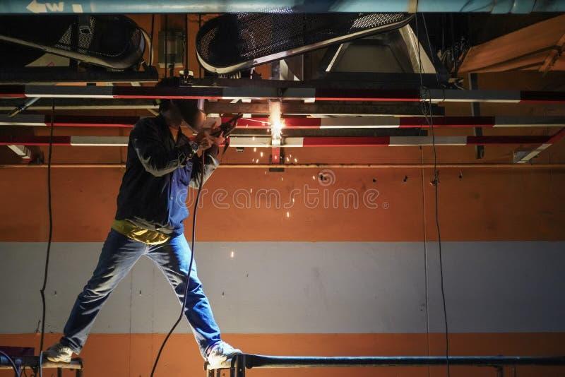 Thailändsk metall för arbetarmansvetsning i konstruktionsplats på natten royaltyfria bilder