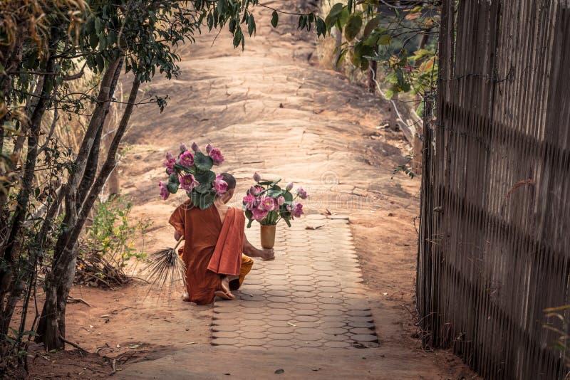 Thailändsk munk med lotusblommablommor i hans händer och traditionella kvast arkivfoto
