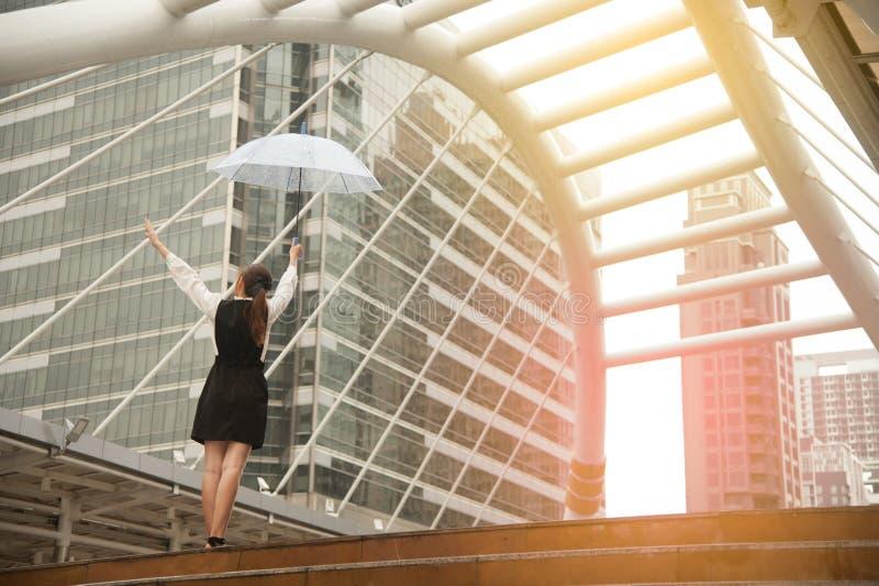 Thailändsk nätt kvinna i den svarta klänningen som rymmer det genomskinliga paraplyet royaltyfri fotografi