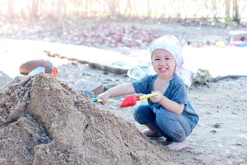 Thailändsk pojke som palying på högen av sand med leksaken och den plast- gaffeln, sp royaltyfria foton