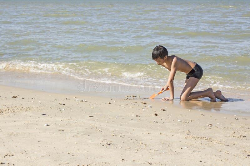 Thailändsk pojkelek i sanden på stranden arkivbilder