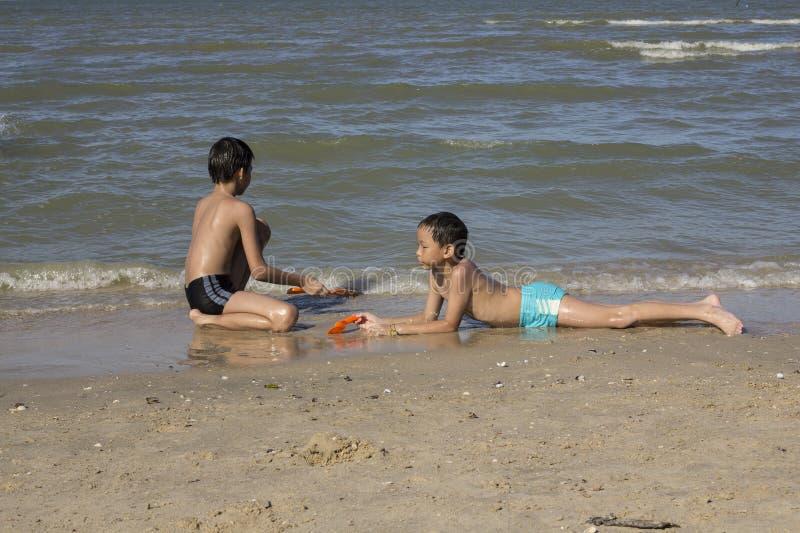 Thailändsk pojkelek i sanden på stranden arkivfoton