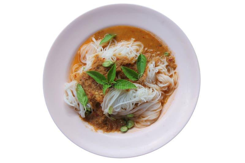 Thailändsk risvermiceller för ånga med röd curry och grönsaker Risnudlar i fiskcurrysås med grönsaker på en rosa skivaisolat royaltyfri bild