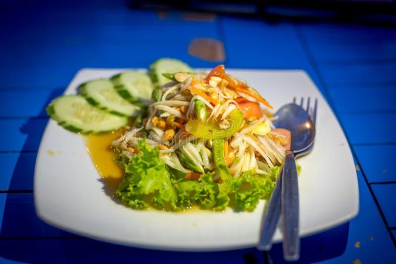 Thailändsk sallad i den vita maträtten med skeden och folk som isoleras på blåtttabellen royaltyfria foton