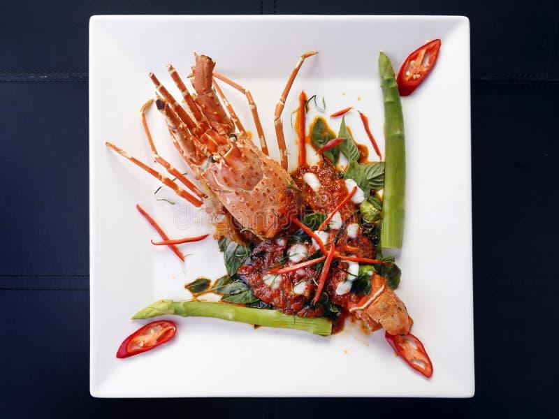 Thailändsk stekt röd curry för stil panna med humret på den vita plattan, isolator fotografering för bildbyråer
