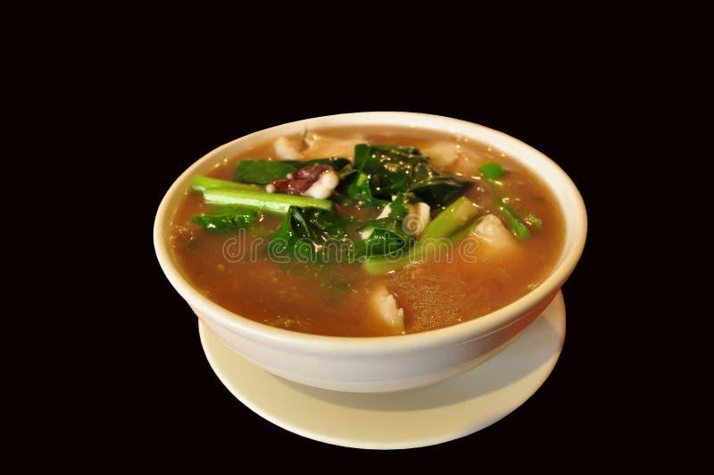 Thailändsk tjock soppa för risskynudlar med bläckfisken i ett vitt slag som isoleras på svart bakgrund arkivfoton