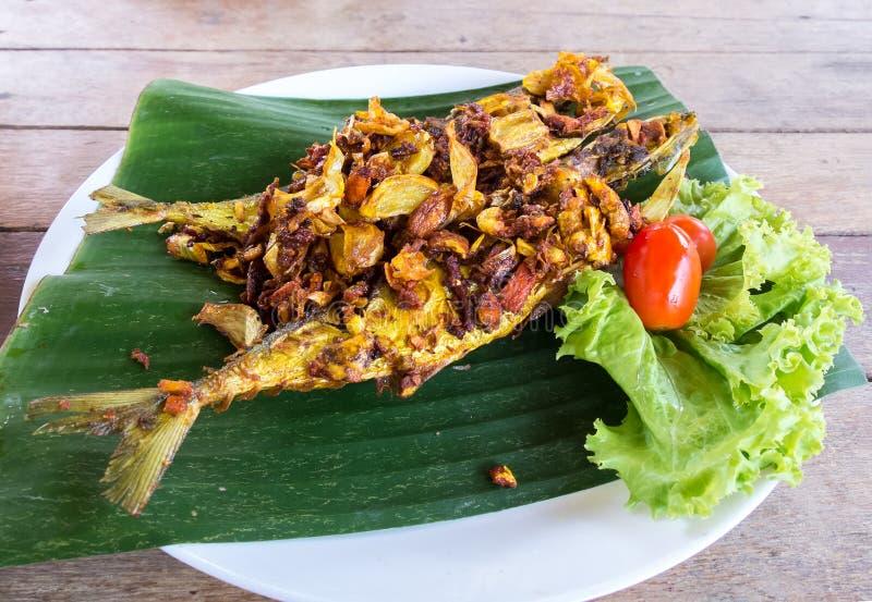 Thailändsk traditionell stil Fried Fishes med örter som gurkmeja och vitlök som tjänas som på bananbladet med tomaten och kål Sun royaltyfria foton