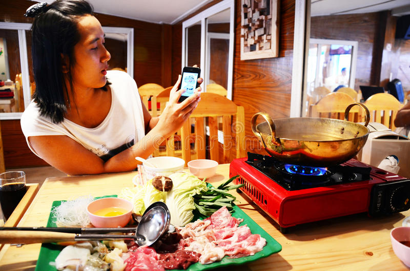 Thailändska kvinnor använder smartphoneskyttefotoet Sukiyaki eller Shabu Shabu royaltyfria bilder