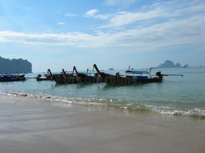 Thailändska långa fartyg ankrade på stranden i Krabi, Thailand fotografering för bildbyråer