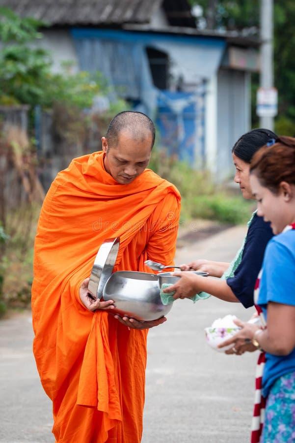 Thailändska munkar mottar mat från byinvånare royaltyfri foto