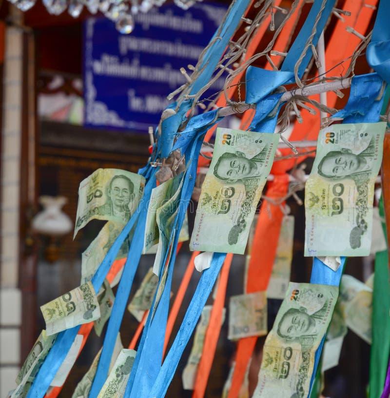 Thailändska pappers- pengar hängde att erbjuda i den buddistiska templet för bra lycka fotografering för bildbyråer