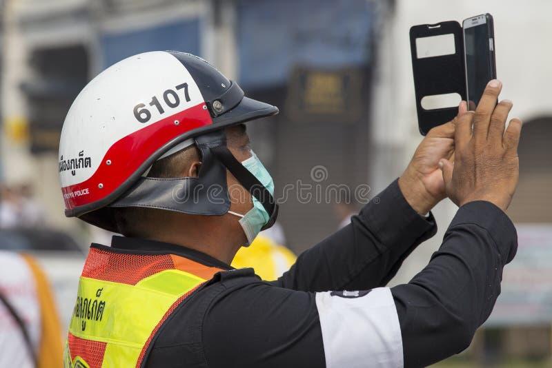 Thailändska polisfotografier på smartphoneprocessionen under den vegetariska festivalen på den Phuket staden thailand royaltyfri bild