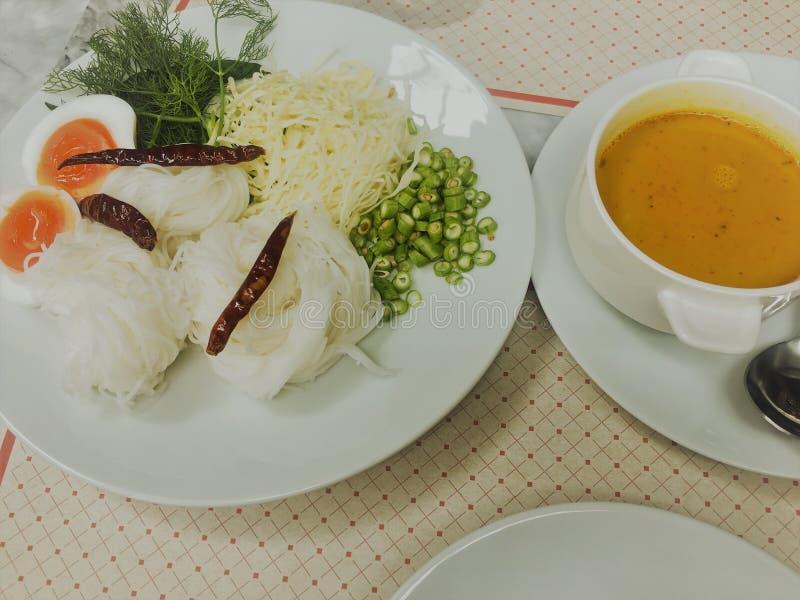 Thailändska risnudlar med krabbacurrysås med grönsaker och det kokta ägget i maträtt arkivbild